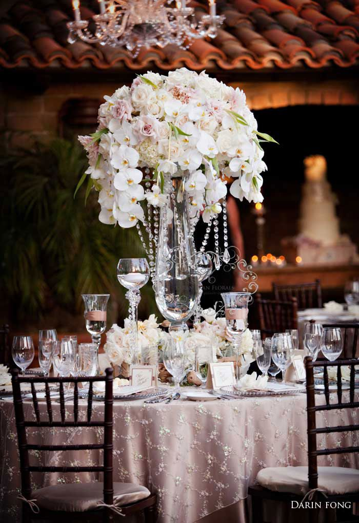 Small lucite risers with black-and-white-striped ribbon bands will be topped with crystal candelabras with votive cups and a large center spray of pink hydrangeas, white phalaenopsis orchids, and double pink tulips and placed in the center of each buffet table.