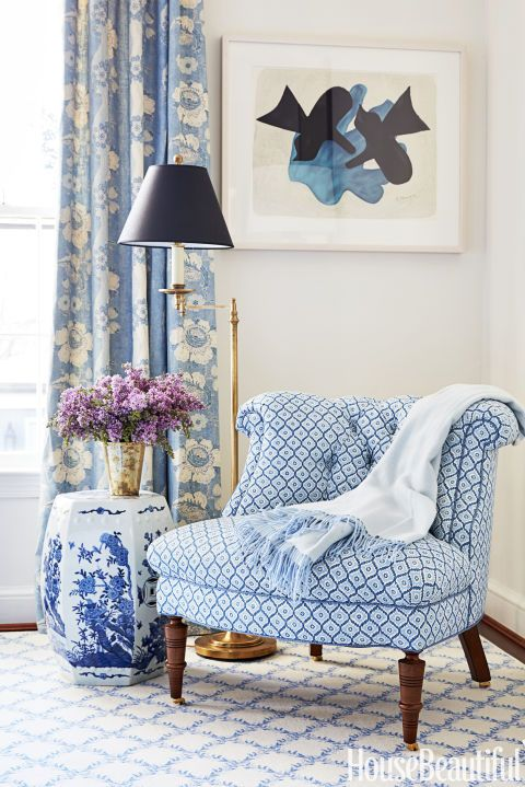 In the blue-and-white master bedroom, a slipper chair in an Elizabeth Eakins fabric offers a place to read a book or slip on shoes.