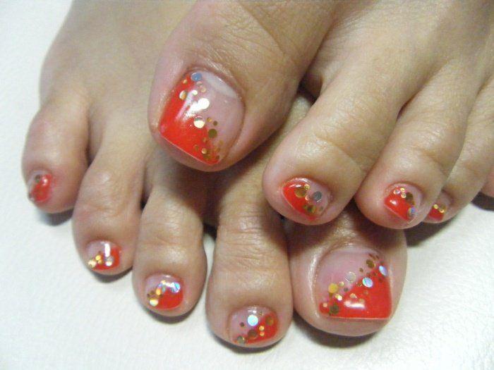 nail art pieds en orange et vernis transparent avec paillettes