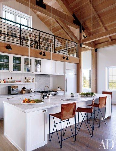 The kitchen of a Martha's Vineyard home designed by Ariel Ashe and Reinaldo Leandro features a Sub-Zero refrigerator, a Wolf range, and Dornbracht sink fittings; the minimalist pendant lights are by Davide Groppi, the Bernard-Albin Gras sconces are by Design Within Reach, and the barstools are by Garza Marfa   archdigest.com