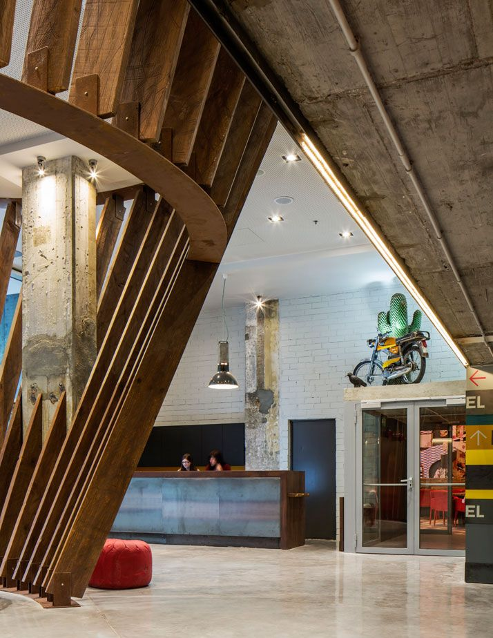 Generator BARCELONA. Hostel reception in timber and blackened steel, exposed concrete columns and vintage 1973 Derbi Spanish motorcycle and collectable and rare Gufram rubber cactus. Photo © Nikolas Koenig.