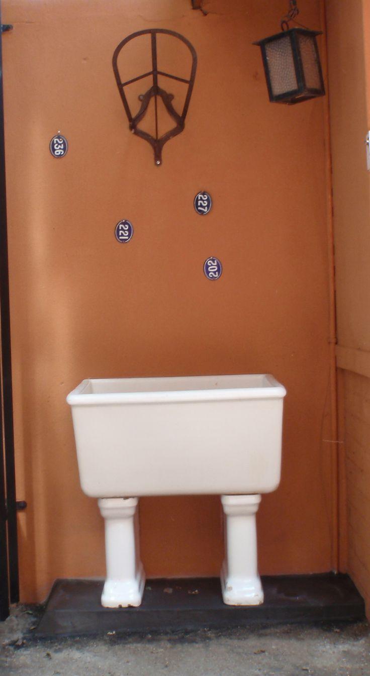 An old wash trough against a blank wall