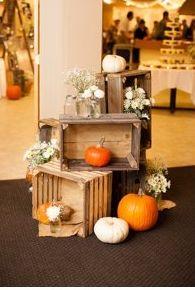 Pumpkins, rustic rates, and small vase arrangements as wedding decor