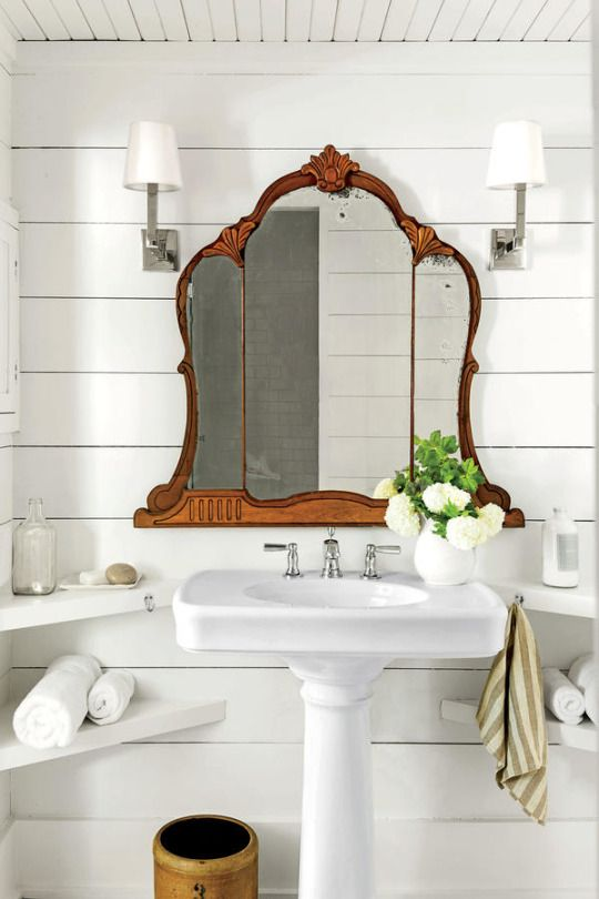 Small White Farmhouse Bath with a mirror salvaged from an old vanity table. Built in corner shelves with a pedestal sink, perfect!