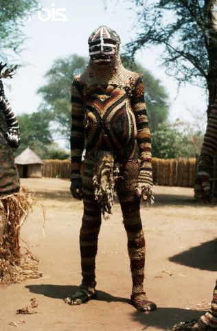 Africa | A man in costume prepares to perform the part of the old man in an African initiation ceremony, border between Angola and Zambia. | Image and caption © Charles & Josette Lenars