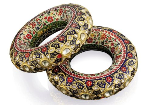 A PAIR OF IMPORTANT INDIAN KADAS : Each anklet set with a series of twelve rose-cut diamond flowerheads on the convex edge to a gold and dark blue enamel background, the sides with floral and foliate polychrome enamel on a white ground to a central line of green and gold decoration, opens by way of screw fitting, Jaipur, 19th century, 694.4 and 687.5 grams, 12.5 cm diameter, 3.3 cm wide