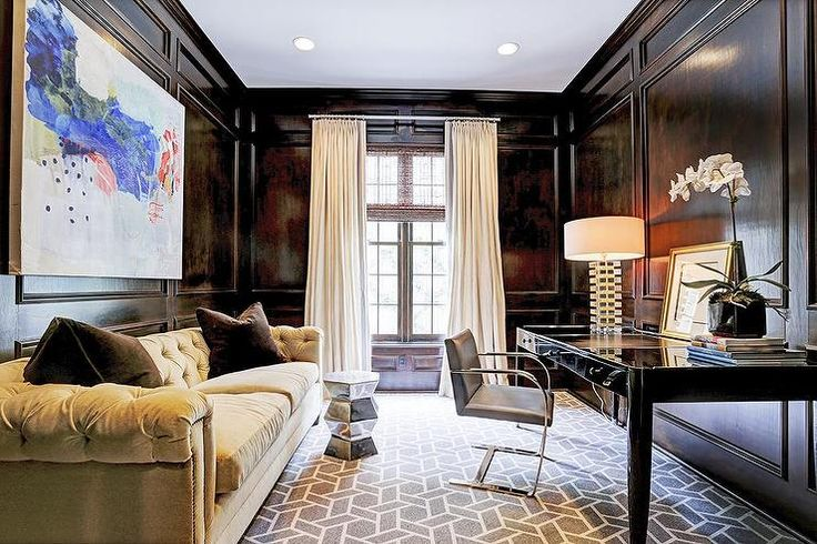 Dark Paneled Den Features Art Over A Camel Colored