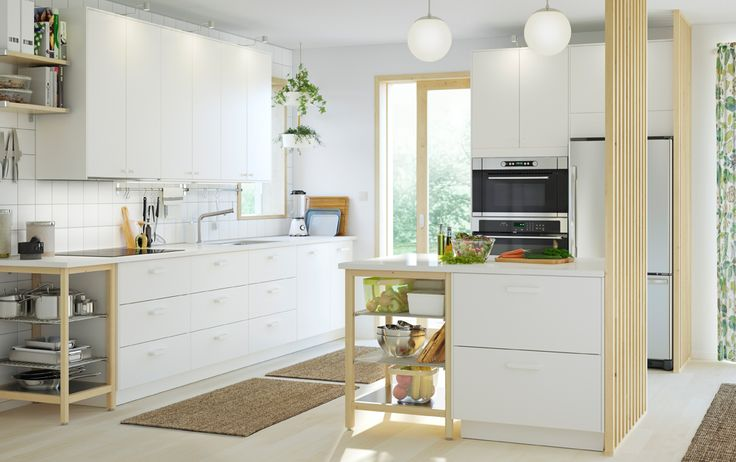 A medium size kitchen with white doors and drawers combined with open storage in solid birch and stainless steel. Shown together with stainless steel  appliances.