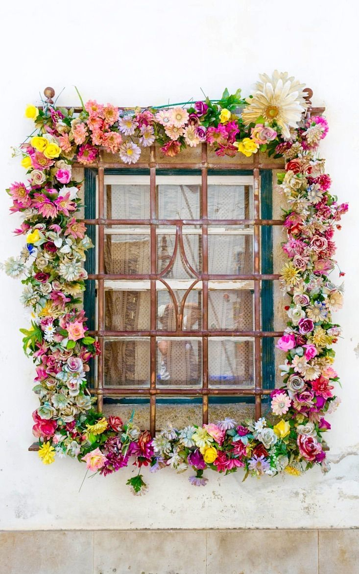 Exterior design ideas and inspiration. Colourful flowers decorate the outside of this window in Obidos, Portugal beautifully.