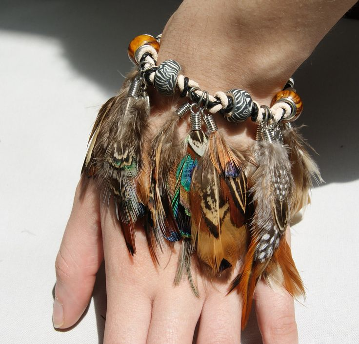 Beads strung onto knotted leather cord with feather charms. Very tribal!
