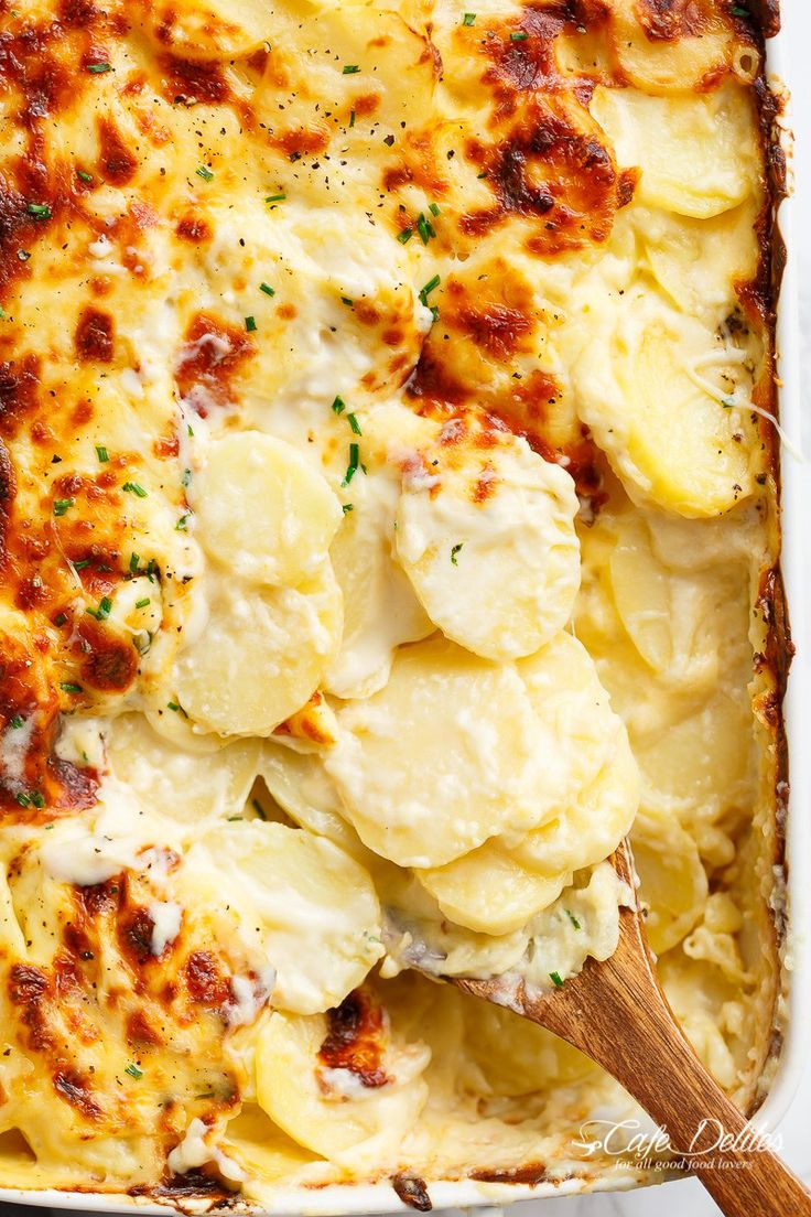 Garlic Parmesan Scalloped Potatoes layered in a creamy garlic sauce with parmesan and mozzarella | http://cafedelites.com