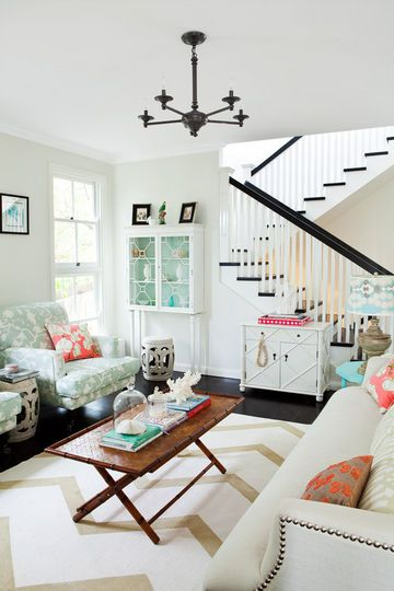 chevron rug, nailhead trimmed sofa, black and white banister, pops of color… love it all in this crisp, chic space