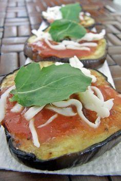 Rodajas de berenjena a la parrilla cubiertas con salsa de tomate, queso mozzarella y parmesano. La versi