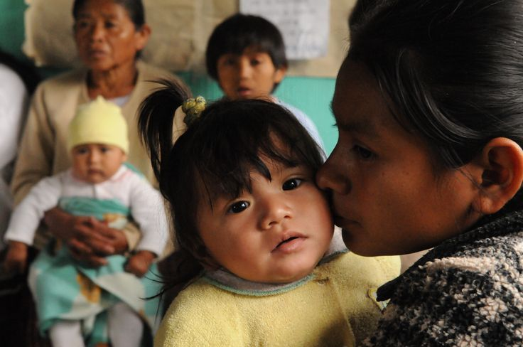 A woman kisses her infant daughter while they wait for a routine check-up at a health centre in the community of Sacanillá in Cobán Municipality. © UNICEF/NYHQ2012-2238/SUSAN MARKISZ