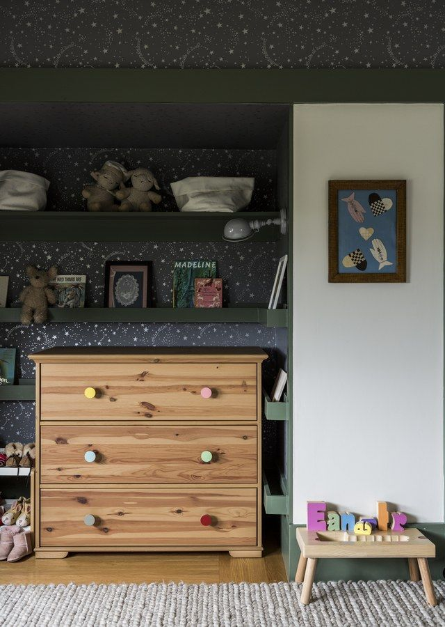 Merrill upgraded a no-fuss IKEA dresser with custom knobs, then paired it with Tapet Café wallpaper and a RH rug in the nursery. A framed early American valentine hangs on the wall.