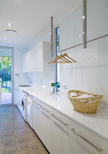 glamorous white laundry room - great idea for hanging rails