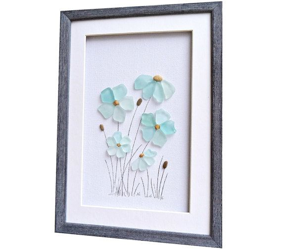 A genuine sea glass art that depicts an image of flowers in gentle pastel colors. Beautiful pastel beach home décor! Great idea for birthday or new home housewarming gift. The sea glass colors are aqua, turquoise, blue sea foam, sea mist color. This fine art was created using sea glass and pebbles that I collected by hand from the local beaches near Varna, Bulgarian Black Sea coast.  Size: 20 cm x 28 cm / approx 8 x 11 /  Framed with a white matting and custom made wooden frame in v...