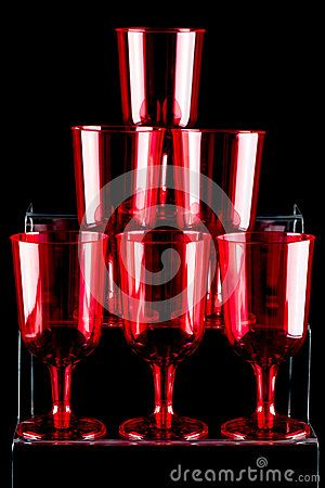 A close up of red plastic stemmed glasses on a dark background