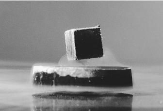 A magnet is hovering over a superconductor, demonstrating that magnetic fields cannot penetrate the superconductor, known as the Meissner effect.