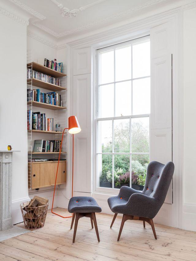 Un coin bibliothèque bien pensé agrémenté d'un fauteuil capitonné gris et son repose-pieds assorti