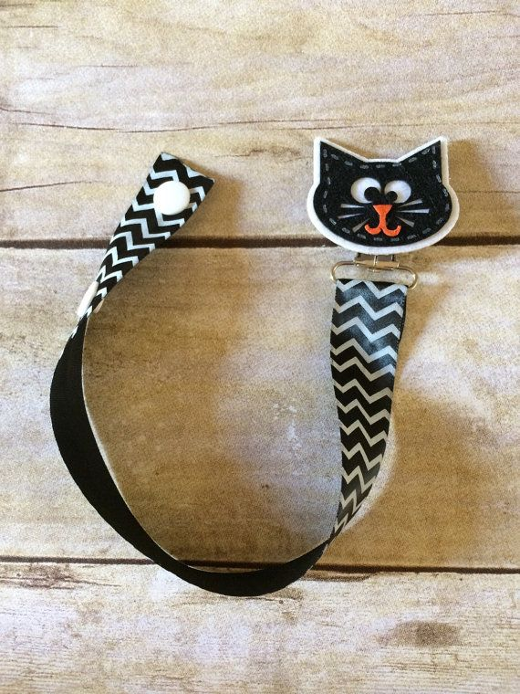 This is a black cat pacifier clip. Great for Halloween. Made out of black ribbon with white chevron. The pacifier is held in with snaps located at