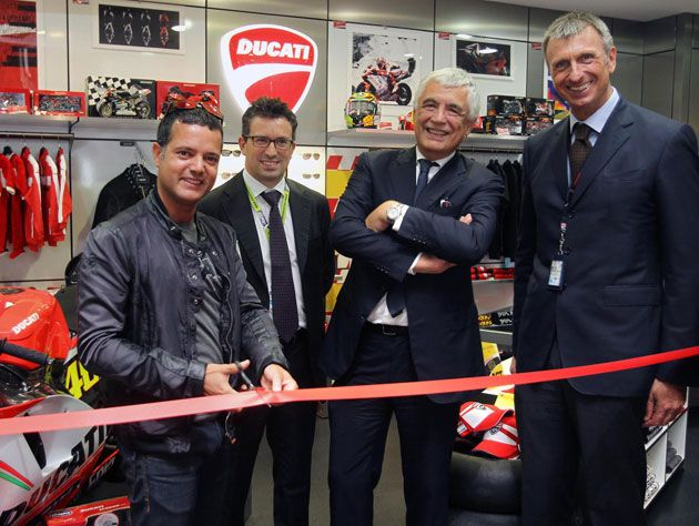 The symbolic ribbon cutting at the new Ducati Shop was attended by Gabriele Del Torchio, CEO of Ducati Motor Holding, Lucio Attinà, Manager of Ducati Motor Holding's BU Apparel & Brand Development, Marco Passoni, Managing Director of Meridian Duty Free, and Andrea Geretto, Non-Aviation Sales and Marketing Manager at Venice's Marco Polo Airport. A little extra Ducati passion was injected into the inauguration ceremony of the latest store with Valentino Rossi's Ducati Desmosedici GP12…