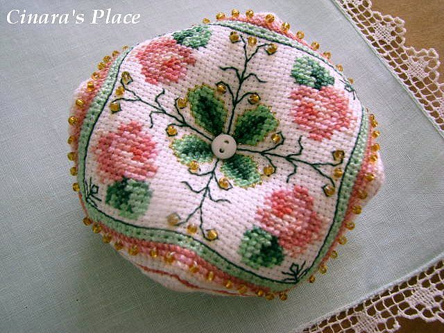 This 8 sided rose pin cushion is called a biscornu. They are usually worked in cross stitch and have become very collectible.