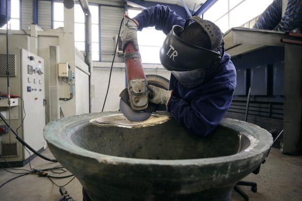 An employee of the Bodet Company restores an old bell at the plant of Trementines, western France. Préparation et ponçage d'une cloche usée par le battant avant recharge du point de frappe par un employé Bodet dans l'usine de Trémentines. Crédit photo : AFP - Gettyimages. http://www.gettyimages.fr/detail/photo-d'actualité/an-employee-of-the-bodet-company-restores-an-old-photo-dactualité/480795679