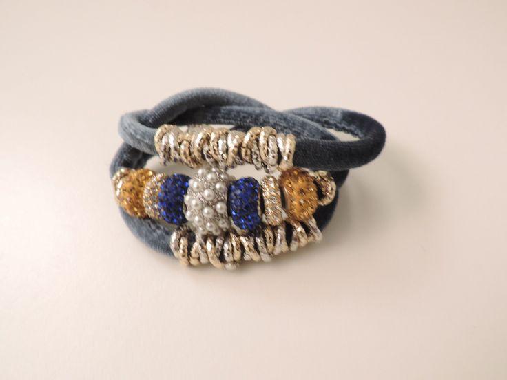 Bracciale in velluto di colore azzurro tiffany con charms a contrasto dorati, giallo oro e blu intenso. Chiusura gioiello con calamita