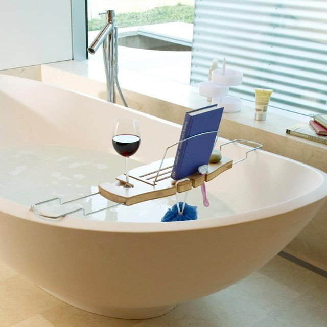 """Designed by Luciano Lorenzatti, the Umbra Aquala Bathtub Caddy is the ultimate accessory for rest and relaxation. Made from bamboo, a highly renewable resource, the expandable Umbra Aquala Bathtub Caddy has a built-in wine glass holder and foldaway book support. 8.5""""w x 28"""" l x 1.5"""" h. Please allow 1-2 weeks for shipping."""