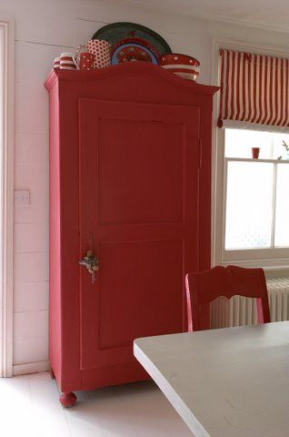 Scandinavian red cupboard with patterned dishes on top.  Love it.