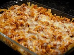 Burrito Casserole - 1 lb ground beef, 1/2 chopped onion, 1 pkg taco seasoning mix, 6 lg flour tortillas, 1 can refried beans, 3 c shredded cheese, 1 can cream of mushroom soup, 4 oz sour cream