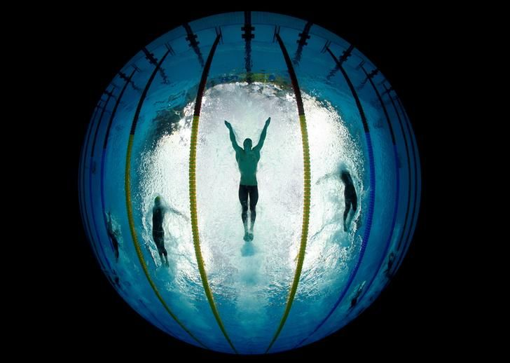 """Michael Phelps (C) of the U.S. swims the butterfly stroke during his team's victory in the men's 4x100 meters medley relay at the National Aquatics Center during the Beijing 2008 Olympics in China August 17, 2008. Wolfgang Rattay: """"Phelps was expected to beat the gold medal record of U.S. swimmer Mark Spitz, who won seven golds during the 1972 Munich Olympics. I bought the 8mm round shot lens for this particular picture. I wanted to mark his new record by making him look like he was swimming…"""