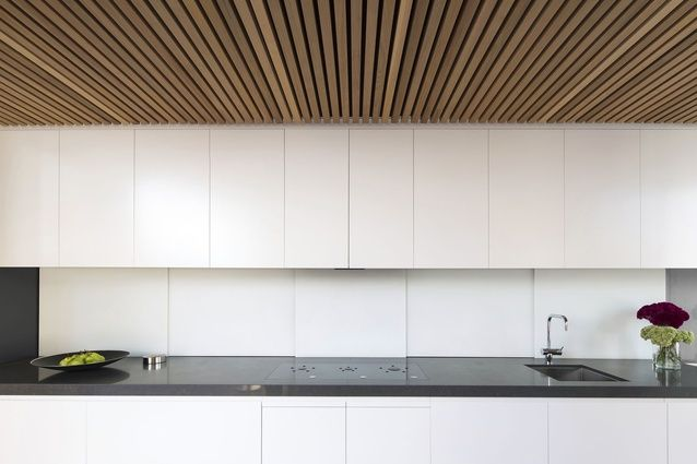The minimalist kitchen runs along one edge of the dining space.