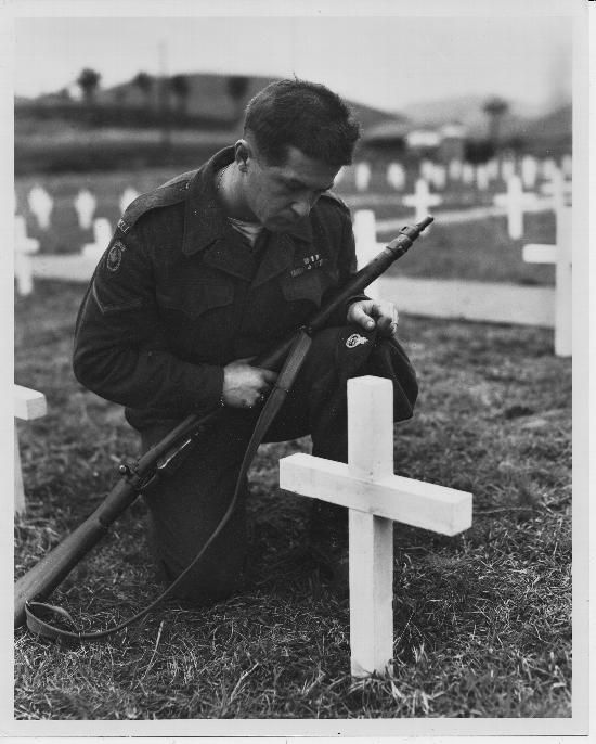 Lance Corporal Robert John Sobol, a member of the Princess Patricia's Canadian Light Infantry, kneels at the grave of a fallen comrade, Private Lloyd K. Wylie, in a United Nations cemetery. Pusan, Korea. April 25, 1951.