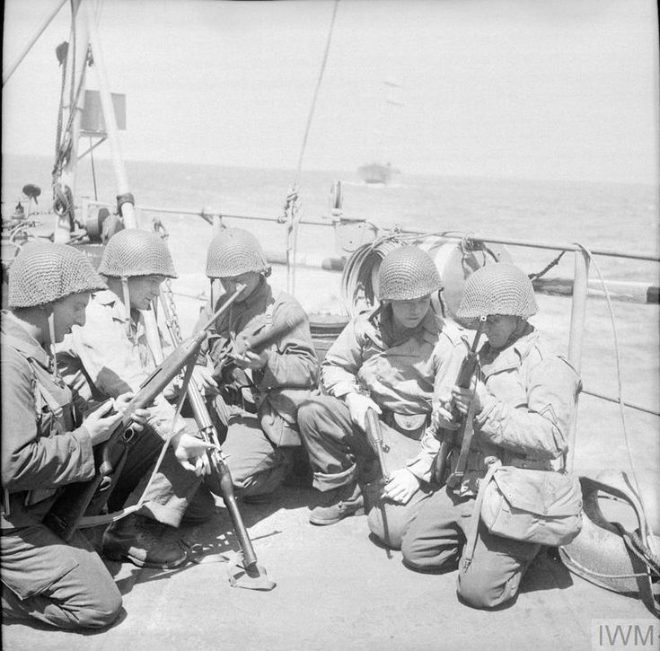 The US 1st Army: American soldiers of a self-propelled artillery unit checking their carbines on board an LCI (Landing Craft Infantry) during the journey to France.
