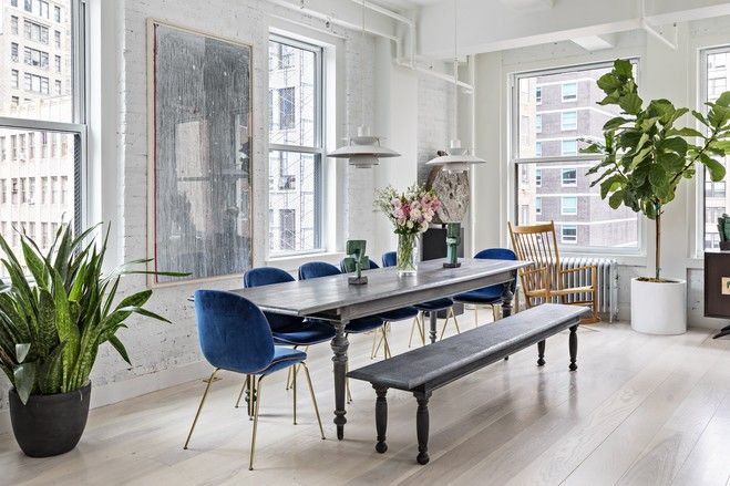 Architect Aaron Schiller of New York-based Schiller Projects knocked down walls to open up the space. He also made some of the furniture, including this oak dining table, which is surrounded by Gubi Beetle Chairs and a wood bench to keep the table open to the living room.