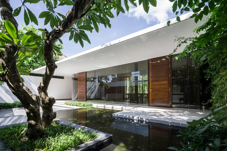 Plant-lined courtyards separate the three single-storey volumes that form this house designed by MIA Design Studio for a coastal city of Vietnam