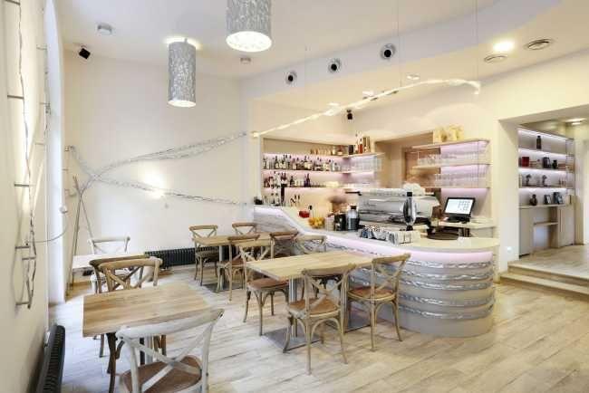 Po vstupe do prednej miestnosti zaujme pozornosť dominantný barový pult s veľkým lesklým kávovarom.