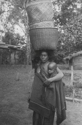 Indonesia, Sumatra ~ Portret van een Karo Batak vrouw met haar kind in een draagdoek en manden op het hoofd Date 1910-1930 Source Tropenmuseum