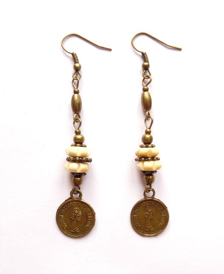 Örhängen i brons med gulvita pärlor av jakben.  Längd: 7,5cm