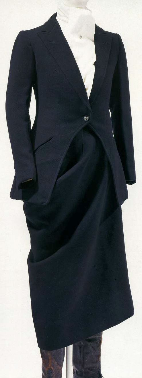 Костюм для верховой езды. Крид, 1900-е. Черная шерсть с саржевым переплетением, приталенный жакет с высоким вырезом спереди, юбка для езды в дамском седле с согнутым правым коленом, юбку надевали поверх брюк-галифе.