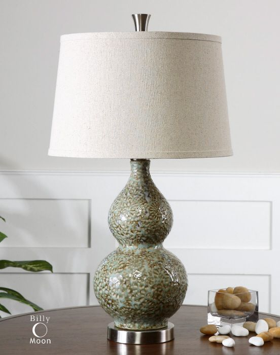 Dimpled ceramic finished in pale green ivory glaze with mottled brown undertones and brushed aluminum accents the round tapered hardback shade is a light