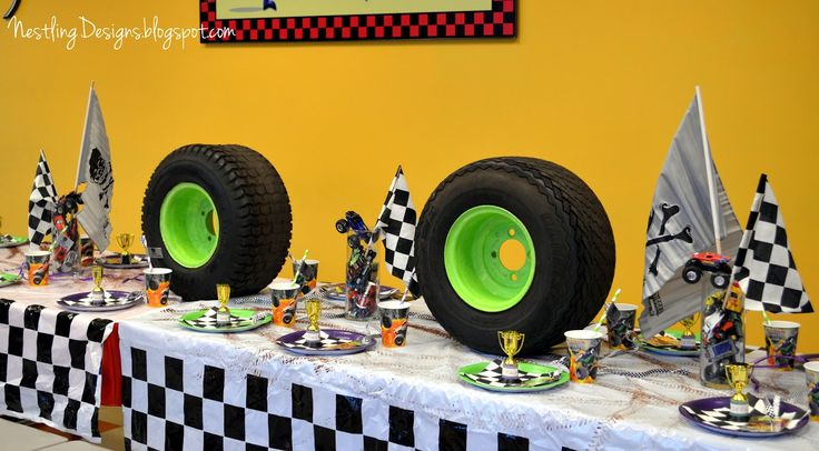 Monster truck table: like cars in clear container with truck on top and painted tire treads on tablecloths