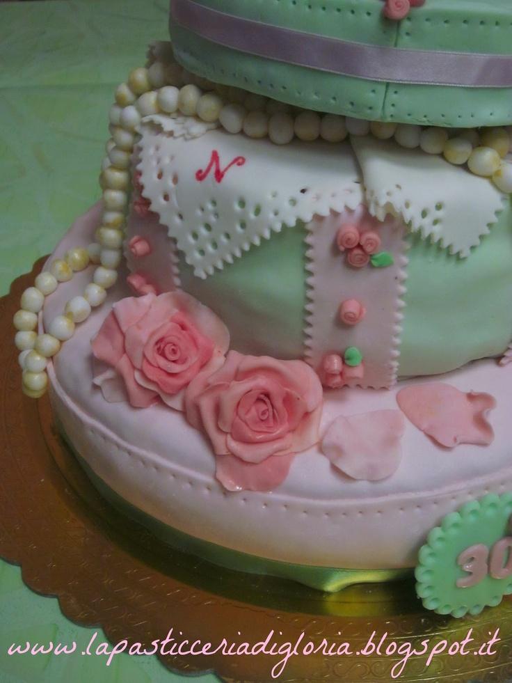 Mi aveva conosciuta tramite il blog e voleva che le realizzassi io la torta...così, prima per email, poi incontrandoci di persona abbiamo cercato di elaborare l'idea e mi sono messa subito all'opera ^___^  La torta doveva parlare di una ragazza alla moda, amante di gioielli e accessori...così abbiamo pensato a questa torta a due piani, dove il secondo doveva rappresentare una scatola portagioielli...e io spero di aver reso bene l'idea :)