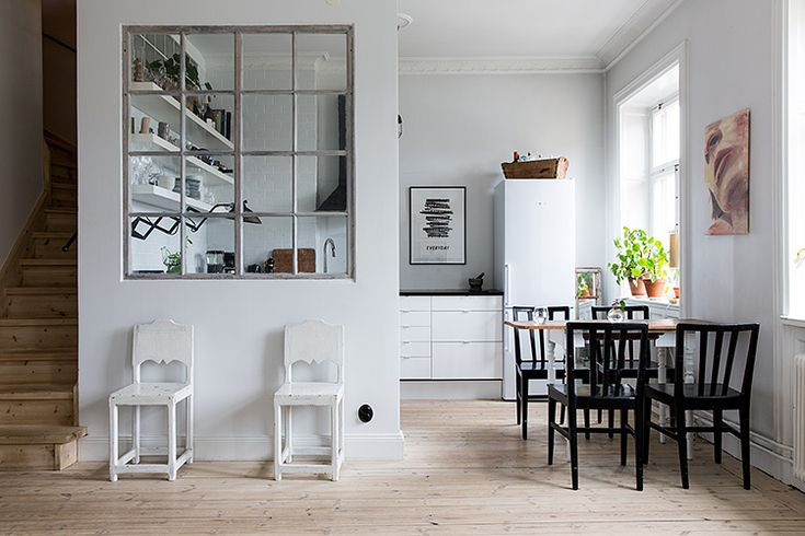 Inner windows - view into kitchen from living room. Love how the long narrow dining table is pushed against the wall between windows. Black chairs add a splash of distinction to the otherwise monochromatic white space. Additional chairs are same white as the half-wall, blending right in!