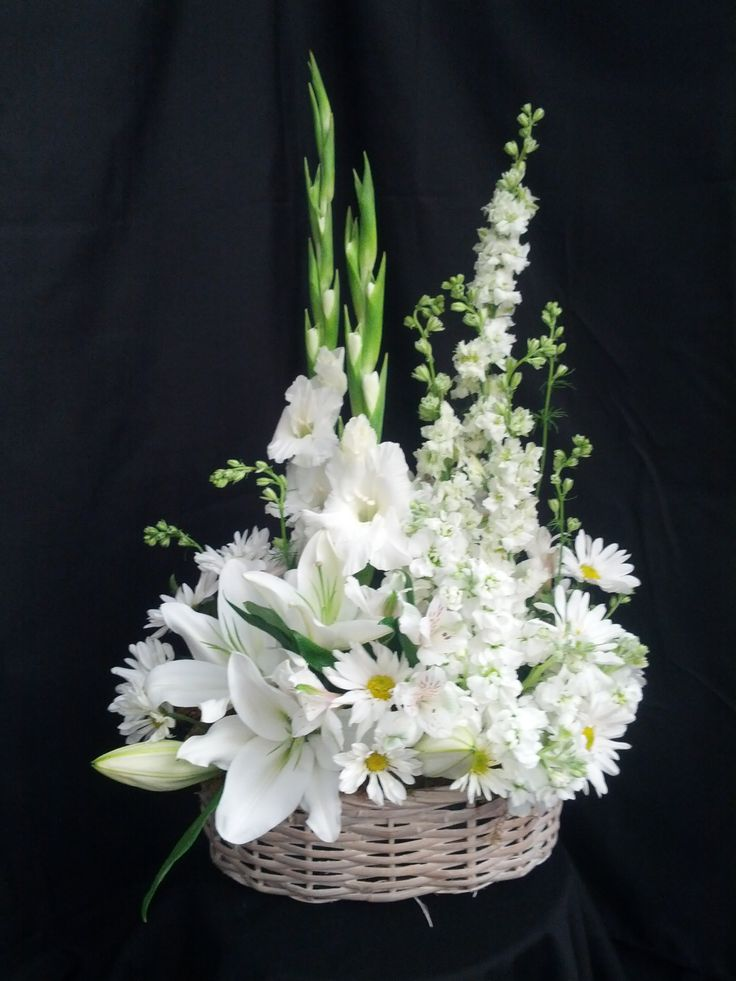 This arrangement is in a white wash handle basket. It has 2 gladiolas, 5 larkspur, 3 daisy poms, 5 stock, 2 oriental lillys, 3 alstromeria, moss, myrtle, leather and salal.