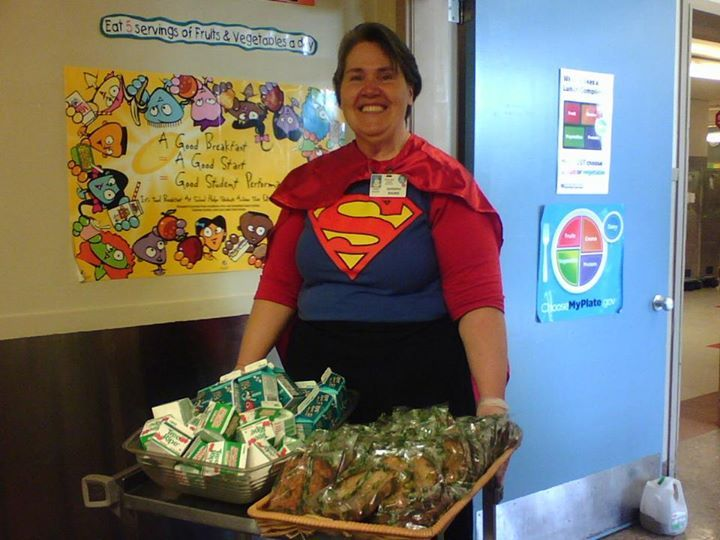 "Portland Public Schools Nutrition Services: ""Today we celebrated Lunch Hero Day. Many of our employees are more than Lunch Heroes, many are Breakfast Heroes too! Here is Super Barbara at Faubion ready to serve students breakfast."""