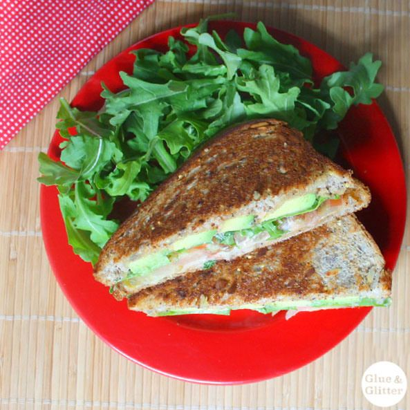 Grilled avocado sandwich with fresh tomato and arugula and spicy ...