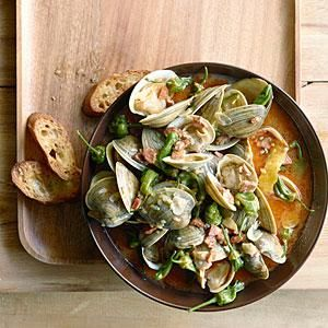 For a dinner party, bring this pot of clams--rich with peppers and smoky sausage--to the table and serve with crusty bread to sop up the juices. If you can't find small Padróns, which can be eaten stems and all, cut stems from larger ones before cooking--or sub in chopped green bell peppers.